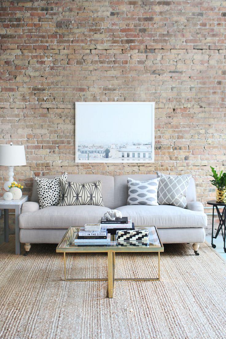 Sofá cinza claro na parede de tijolos