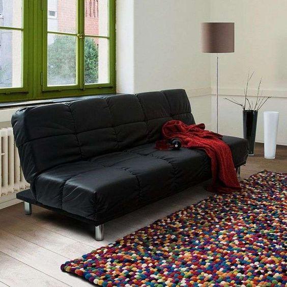 sofá preto com tapete colorido