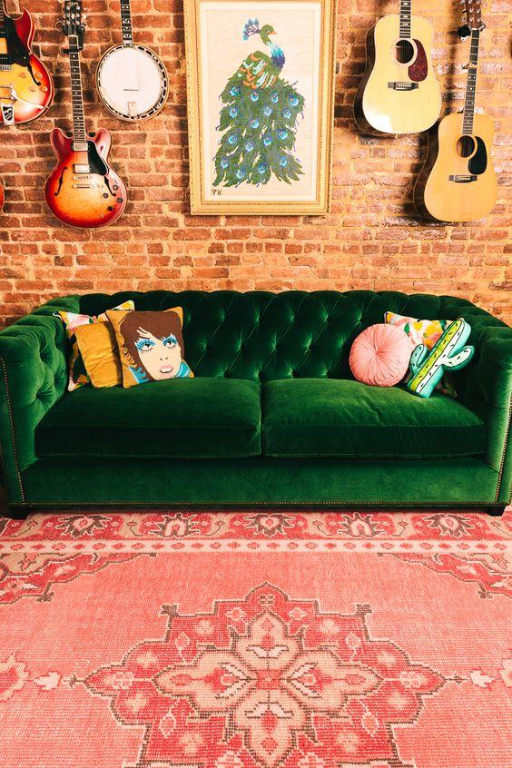 Sofá verde com almofadas coloridas e descoladas