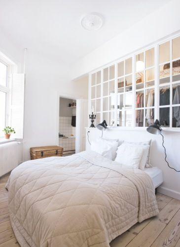 Closet atrás da cama com janela de vidro