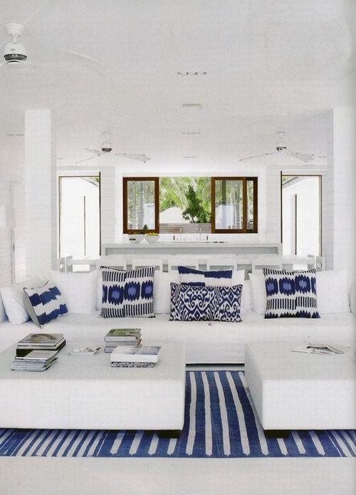 Sofá branco com tapete listrado azul e almofadas azuis