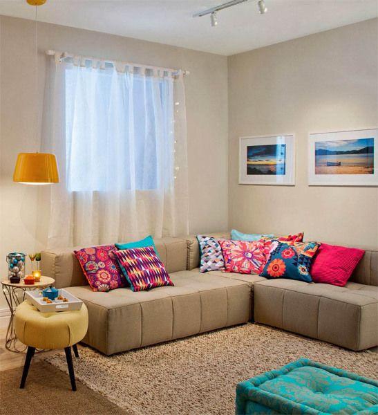 Sofá bege com almofadas coloridas de crochê