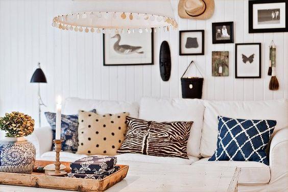 Sofá branco com almofadas animal print e de bolinha.