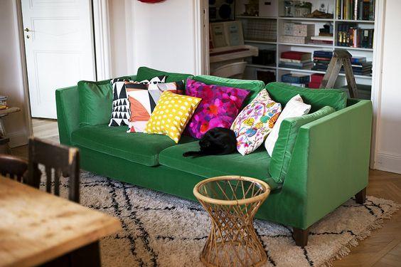 sofá verde com almofadas coloridas