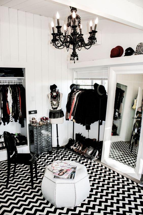 closet branco com tapete preto e branco, cadeira e lustre pretos