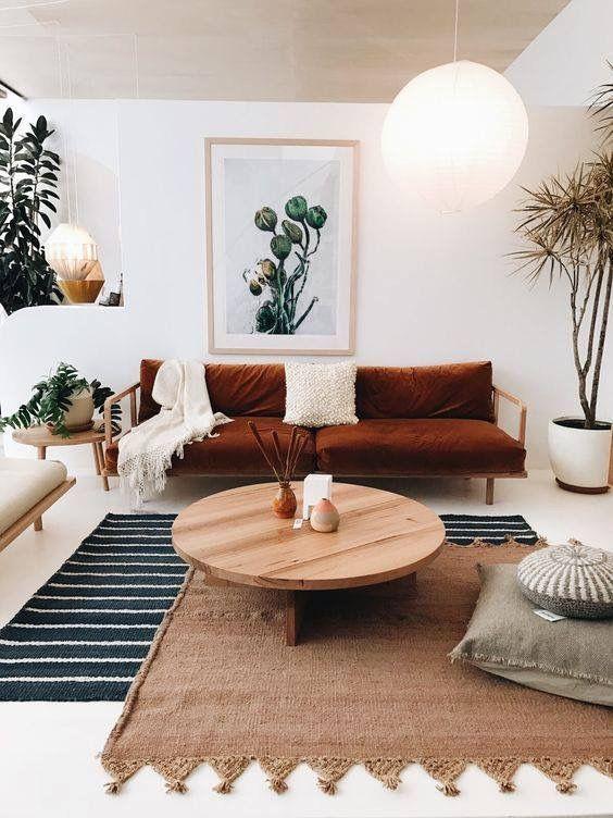 Almofada para sofá na cor branca com algumas almofadas no chão para dar mais conforto.